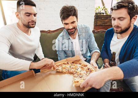 Young Men taking tranches de pizza Banque D'Images