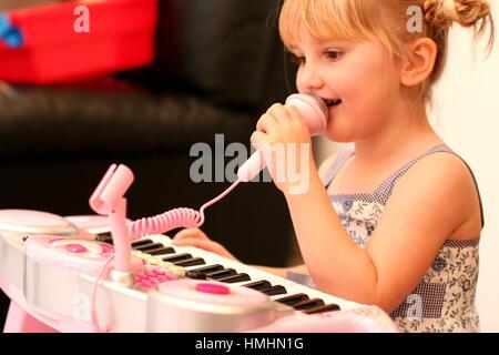 Petite fille enfant kid bouche micro chant, piano clavier jouet jeu pigtails, leçons de musique, de l'apprentissage, Banque D'Images