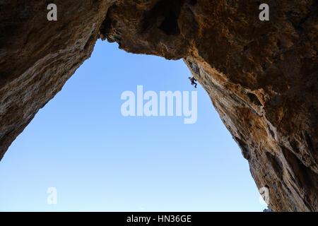 Jeune homme randonnées le long des rochers Banque D'Images