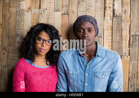 Portrait of couple standing contre mur en bois en café Banque D'Images