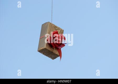 Coffrets cadeaux qui s'accrochent sur les fils suspendus et des réseaux. Décorations de rue avant Noël, Nouvel An Banque D'Images