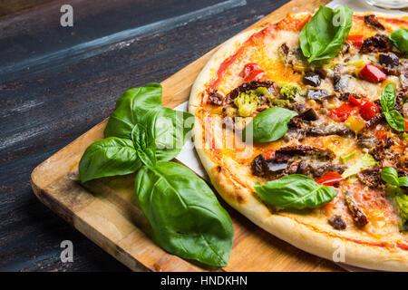 Pizza fraîche servi sur table en bois. Profondeur de champ. Banque D'Images