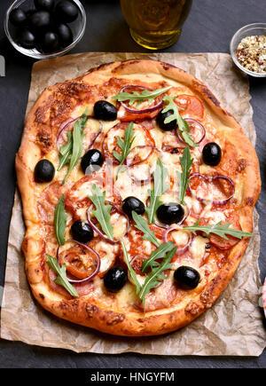 Pizza à la tomate, olives et salami sur le papier Banque D'Images