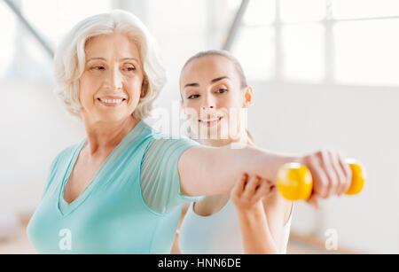 Heureux femme agréable l'entraînement avec un haltère Banque D'Images