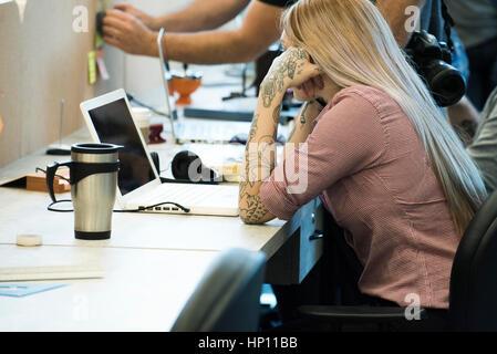 Femme se concentrant sur travailler dans l'espace de bureau partagé Banque D'Images