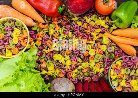 Pâtes colorées sur une table avec des légumes frais (betteraves, verts, carottes, tomates, poivrons). Concept d'aliments Banque D'Images