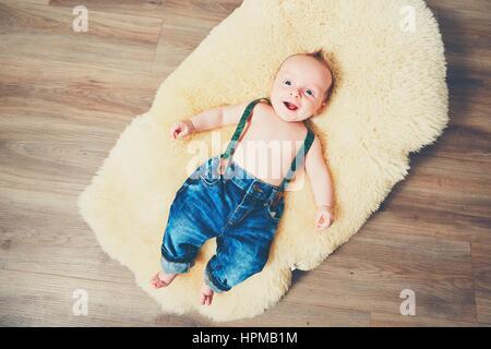 Petit garçon à la maison. Adorable bébé reposant sur la couverture de fourrure en bois sur l'étage. Banque D'Images