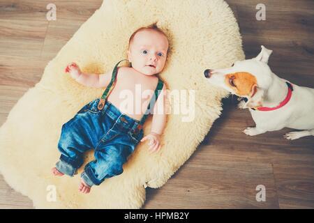 Petit garçon et le chien à la maison. Adorable bébé reposant sur la couverture de fourrure. Banque D'Images