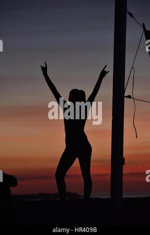 Silhouettes de joueurs de volley-ball féminin volley-ball pratique sur une plage au coucher du soleil à Mission Banque D'Images