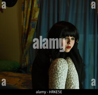 Triste jeune femme prisonnière dans sa chambre à coucher Banque D'Images
