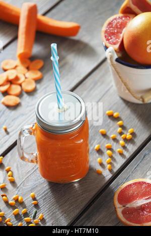 Le pamplemousse et le jus de carotte en verre sur la table Banque D'Images