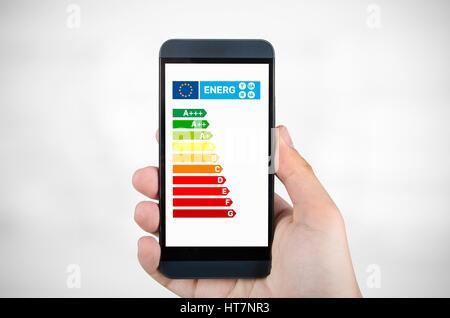 Man holding smartphone avec tableau de l'efficacité énergétique. Dans l'épargne home concept Banque D'Images