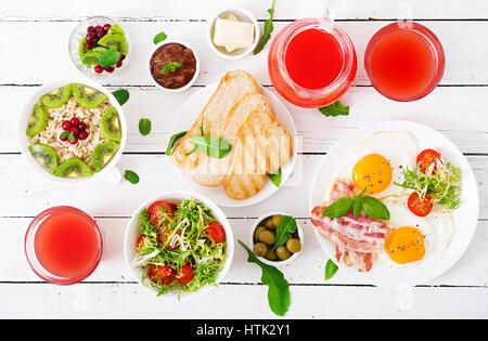 Petit-déjeuner anglais - œuf frit, tomates et bacon. Le petit-déjeuner pour deux. Le gruau. Mise à plat. Vue d'en Banque D'Images