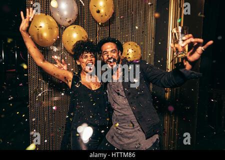 Photo de couple énergique de danser dans la boîte de nuit. Young man and woman having fun at pub partie. Banque D'Images
