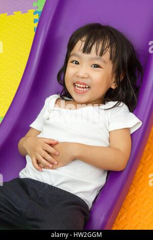 Chinois asiatique petite fille jouant sur la diapositive à une aire de couleur. Banque D'Images