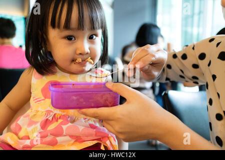 Mère fille asiatique alimentation Aliments pour enfants dans un restaurant. Banque D'Images