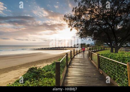 Walker tôt le matin sur l'Esplanade promenade de plage de Bargara, Bundaberg, Queensland, Australie Banque D'Images