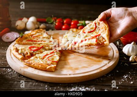 Tranche de pizza en femme main sur la table avec pizza Banque D'Images