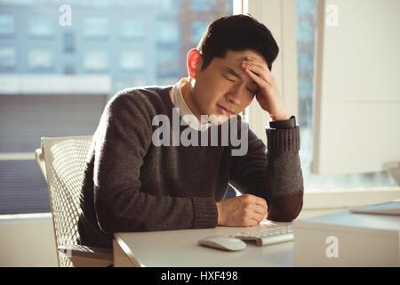 Déprimé male executive sitting at desk in office Banque D'Images