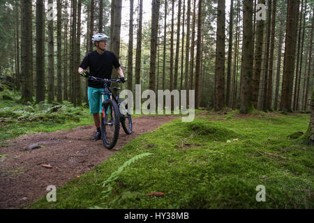 La Suède, vastergotland, lerum, mature man with bicycle in forest Banque D'Images