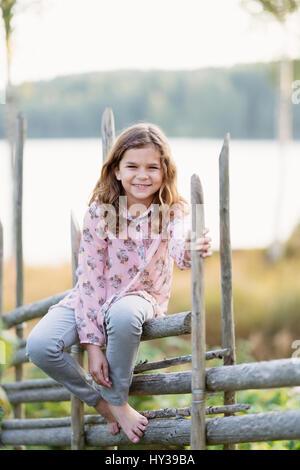 La Suède, vastmanland, hallefors, bergslagen, portrait of smiling girl (8-9) sitting on fence Banque D'Images