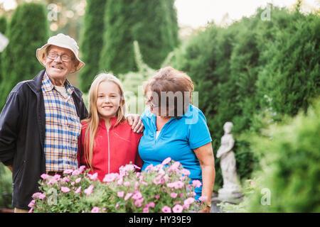 La Suède, vastmanland, hallefors, bergslagen, girl (12-13) avec les grands-parents posant dans jardin Banque D'Images