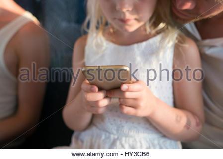La Suède, Girl (6-7) et le père using cell phone Banque D'Images