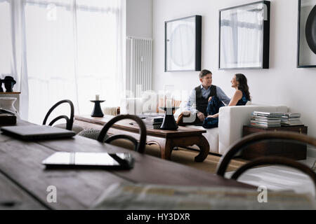 Allemagne, couple sitting on sofa in living room Banque D'Images