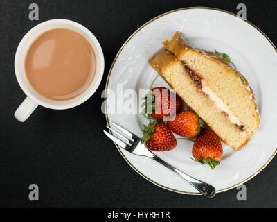 Gâteau éponge victoria au four avec des fraises sur un fond noir Banque D'Images
