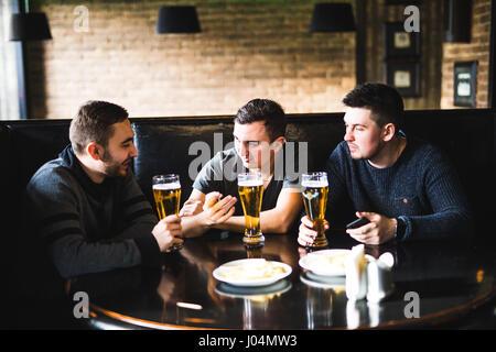 Trois jeunes hommes en vêtements décontractés sont parler, manger des frites et boire de la bière tout en restant Banque D'Images