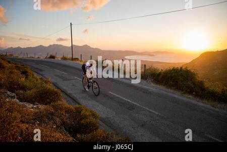 Un jeune homme est la formation road racing bycycle à Calvi, corse. La Corse est la plus montagneuse de l'île Méditerranéenne Banque D'Images