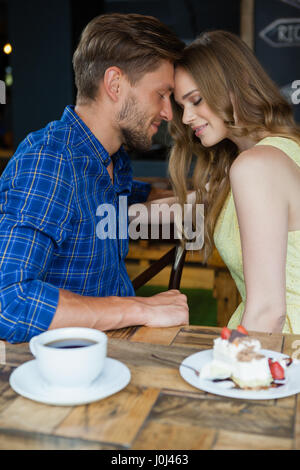 Close up of romantic couple avec les yeux fermé assis sur une chaise de café shop Banque D'Images