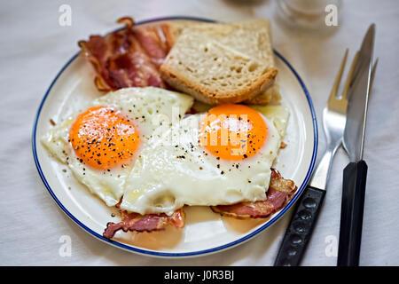 Des œufs sur le lard avec petit-déjeuner, pain, plaque blanche Banque D'Images
