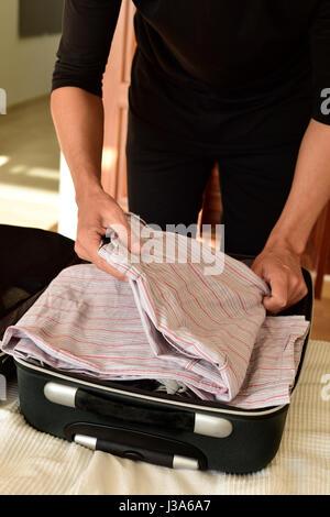 Libre d'un jeune homme de race blanche enfiler ses vêtements dans sa valise ou de les mettre hors tension, sur le Banque D'Images