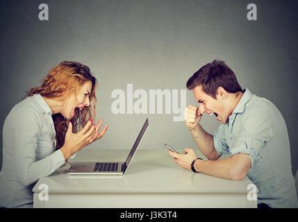 Stressed business woman with laptop sitting at table with angry man de crier sur téléphone mobile. Les émotions Banque D'Images