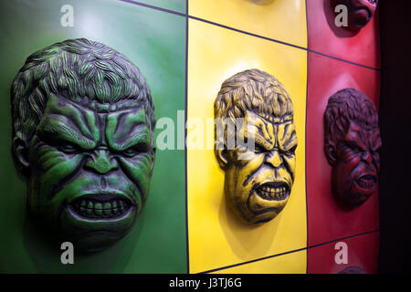 Décoration murale colorée Hulk face à un parc d'amusement. Caractère bd portrait en colère en vert, jaune et rouge Banque D'Images