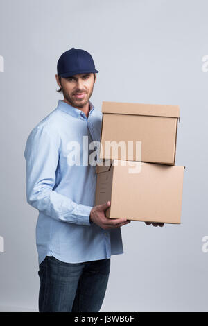 Studio shot of African delivery man carrying boxes Banque D'Images