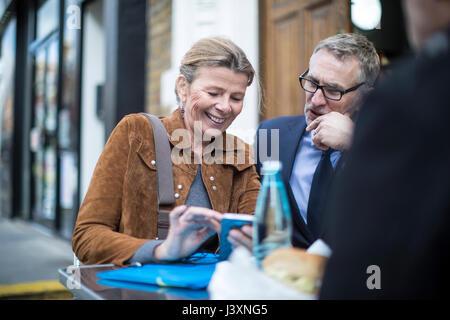 Businesspeople at cafe de la chaussée après avoir déjeuner de travail Banque D'Images
