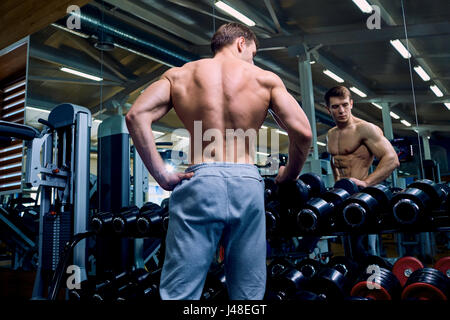 Vue arrière d'un homme sportif avec les muscles dans la salle de sport Banque D'Images