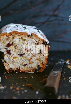 Close-up of Christmas Stollen gâteau sucré avec des raisins secs, des abricots séchés et d'épices sur un fond bleu Banque D'Images
