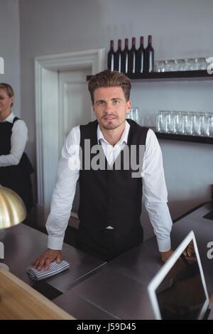 Portrait de barman debout à comptoir de restaurant Banque D'Images