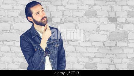Digital composite de hipster réfléchie à l'extérieur contre mur Banque D'Images