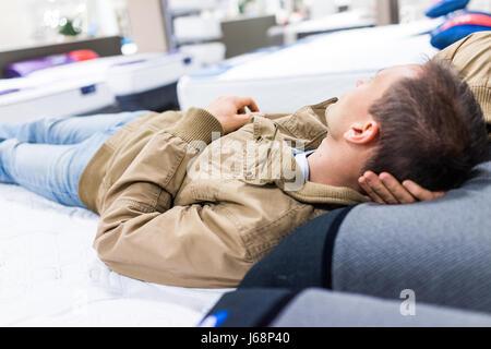 Jeune homme essayer fixant sur le matelas sur l'affichage en magasin Banque D'Images