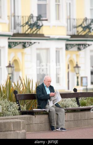 Un homme de prendre le temps de lire le journal du matin sur la promenade de Llandudno en face des nombreux hôtels Banque D'Images