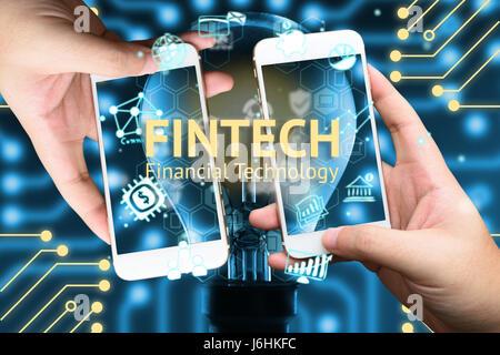Fintech concept. Deux hand holding mobile phone et icônes de la technologie financière. Ampoule Lumière , Infographie Banque D'Images