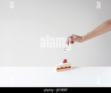 Main tenant une fourche sur le point de manger une tranche de gâteau Banque D'Images