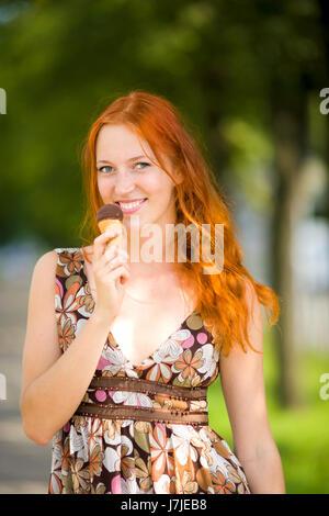 Redhead Woman eating ice-cream journée ensoleillée à l'extérieur Banque D'Images
