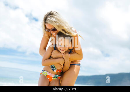 Mère et fille (6-7) embracing on beach Banque D'Images