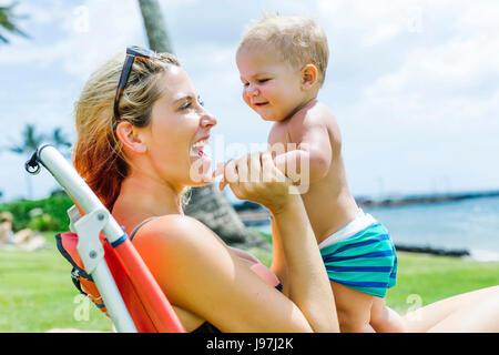 Femme assise sous palmier avec peu de fils (18-23 mois) Banque D'Images
