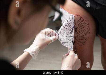Un tatoueur professionnel est présenté avec des croquis sur la partie du corps Banque D'Images